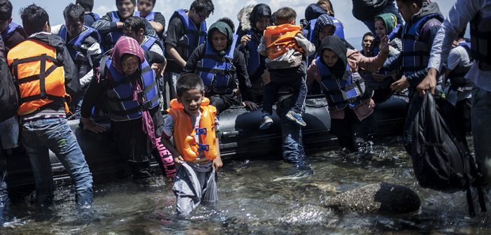 A young afghan boy and other new arrivals transiting through Turkey disembark from a boat on Lesbos, Greece